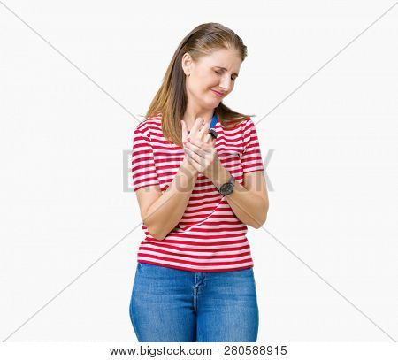 Middle age mature woman wearing casual t-shirt over isolated background Suffering pain on hands and fingers, arthritis inflammation