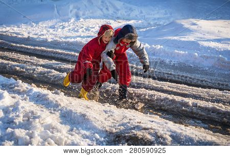 Two Boys In Rainboots Playing With Toy Boat An The Creek Of Melting Snow At Sunny Spring Day, Outdoo