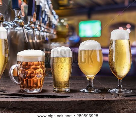 Chilled mugs and glasses of beer on the old wooden table. Pub interior and bar counter with beer taps at the background. Assortment of beer.