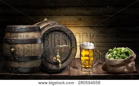 Beer mug and small keg of beer on the wooden table. Craft brewery.