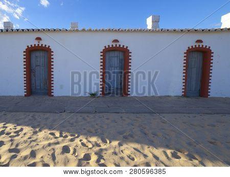 Former whitewashed fishermen huts, converted into tourist facilities at Praia do Barril beach, Tavira, Algarve, Portugal poster