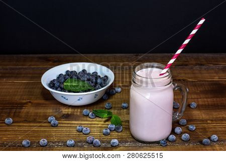 Blueberry smoothie with mint leaf and straw on wooden table