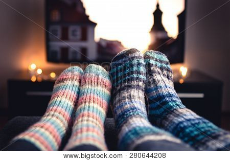 Cozy Woolen Socks. Couple Watching Tv In Winter. Man And Woman Using Online Streaming Service For Mo