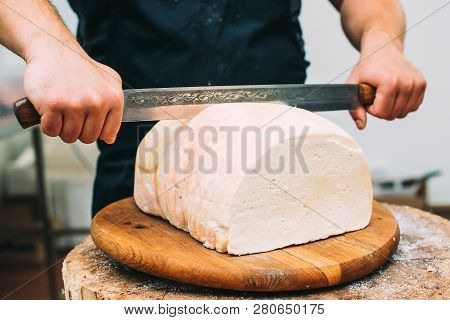 Shopkeeper's Hands Cutting A Head Of White Cheese. Cutting Cheese, Close Up. Artisan Cheese In A Str