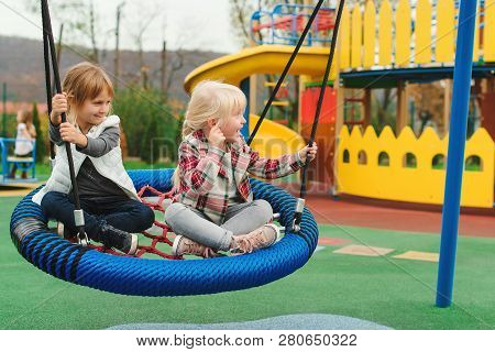 Happy Kids Having Fun On Playground Outdoors. The Best Girl Friends Playing Together. Modern Colorfu