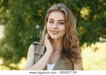 Portrait Of A Charming Girl With A Cute Smile With Natural Make-up In Summer Elegant Clothes Against