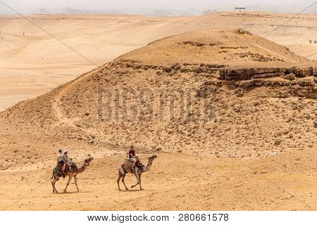 Cairo, Egypt 25.05.2018 - Tourists And Guides Riding Camels On Giza Plateau In The Rocky Desert
