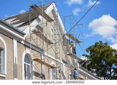 Kyiv, Ukraine - January, 30, 2019:  Contractors Plastering House Facade Outdoor. Painting And Plaste