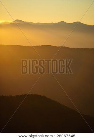 sunrise shining over mountains