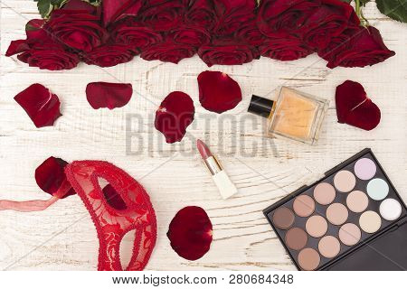 Romantic Carnival Concept. Red Carnival Mask, Bouquet Of Red Roses, Lipstick, Bottle Of Perfume And