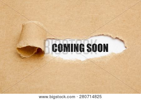 The Phrase Coming Soon Appearing Behind Ripped Brown Paper. Concept About Upcoming Promising Event A