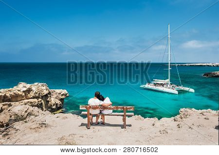 Rear View Of A Couple In Love On Vacation. Honeymoon Traveller Couple Hugging On A Wooden Bench And