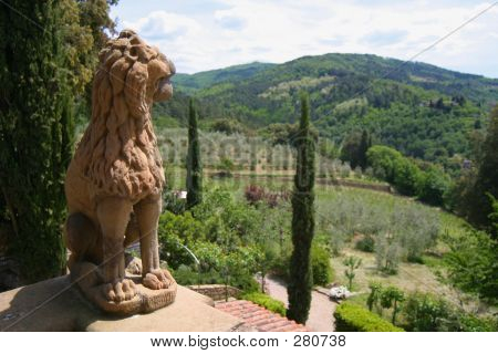 the rolling hills of tuscany viewed from the vignamaggio winery and hotel with a sculptured guardian lion, olive and cypress trees in the foreground. this is the house where leonardo de vinci is believed to have painted the mona lisa, and indeed where she poster