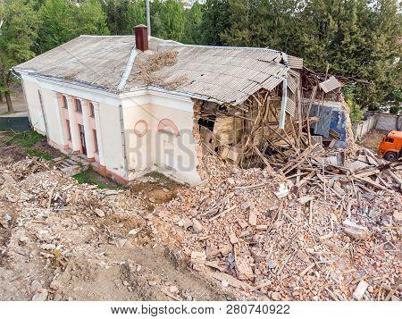 Half Destroyed Brick Building At Demolition Site. Pile Of Debris Of A Destroyed Building