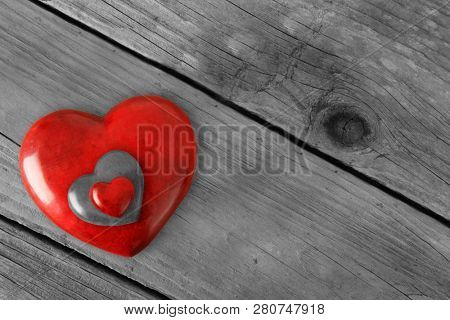 Three Red Valentines stone hearts stacked on a rustic wooden background. Valentine day love concept. February 14.