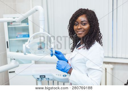 Portrait Of Female Black Dentist In Dental Office. She Standing At Her Office And She Has Beautiful