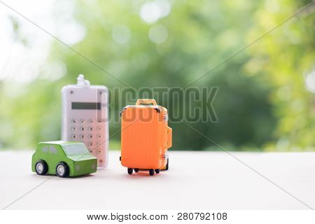 Miniature Toy Car And Miniature Orange Suitcases With Calculator On Nature Background. Concept Of Tr