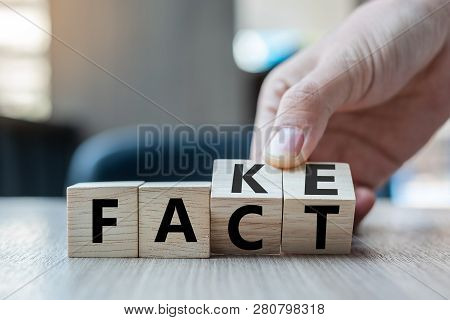 Business Man Hand Holding Wooden Cube With Flip Over Block Fake To Fact Word On Table Background. Ne