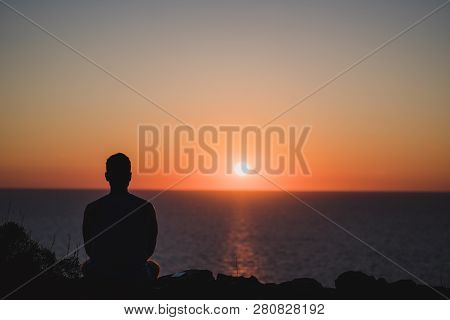 Young Man Looking To The Sunset Over Sea. Enjoying And Relaxing Concept, Full Of Unforgettable Exper