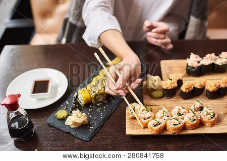 Woman Eating And Enjoying Fresh Sushi In Luxury Restaurant. Female Client Holding Food Sticks And Ea