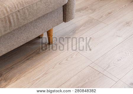 Grey Sofa With Wooden Legs On Lamonate Floor