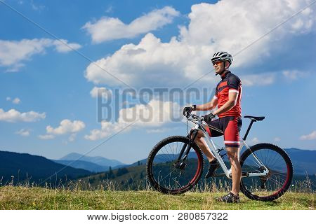 Athletic Sportsman Cyclist Standing With Cross Country Bike On Grassy Valley, Enjoying Beautiful Vie