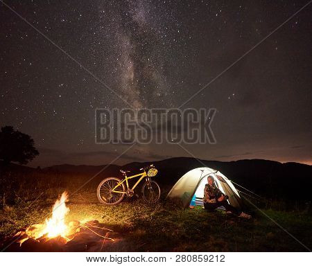 Young Woman Cyclist Enjoying At Night Camping Near Burning Campfire, Illuminated Tourist Tent, Mount