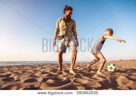 Happy Father And Son Play Soccer Or Football On The Beach Having Great Family Time On Summer Holiday