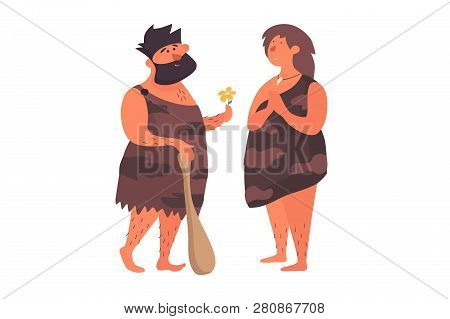 Primitive Man In Love Gives A Flower To His Primitive Girlfriend. Prehistoric People Dressed In Skin