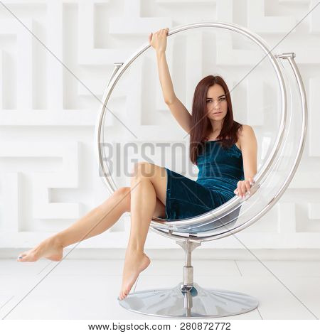 Attractive Young Brunette Woman Wearing Elegant Dress Sitting In A Round Glass Chair