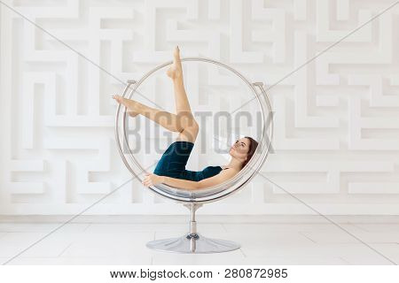 Attractive Young Woman Wearing Elegant Blue Dress Lying On Round Glass Chair In White Room. Futurist