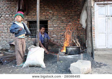 KATHMANDU, NEPAL - JANUARY 7: Worker Sahadev Kumar and his son Siva (left) sharpening tool of a poor area at Old Baneshwor near Bagmati river, January 7, 2009 in Kathmandu Nepal.