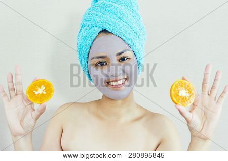Happy Woman With A Clay Mask With Biting Slice Of Orange. Photo Of Attractive Young Woman With Towel