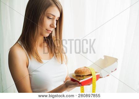 Diet. Woman With Guilty Feeling To Eat A Hamburger