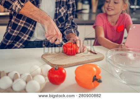 Tall Bearded Dark-haired Man Cutting A Tomato For Salad