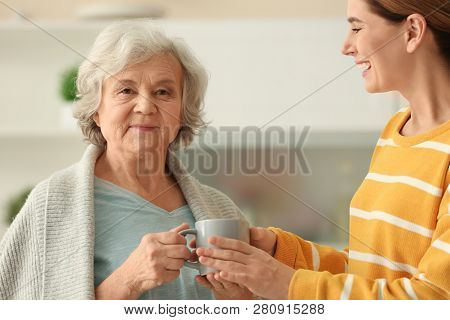 Female Caregiver And Elderly Woman With Cup Of Tea In Kitchen