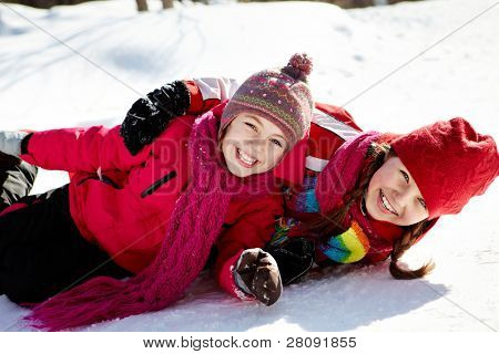 Happy girls in winterwear looking at camera while playing outside