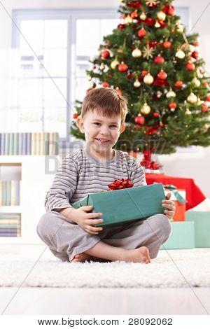 lachend Boy sitting on Floor with gewickelt Weihnachtsgeschenk im Morgenlicht.?