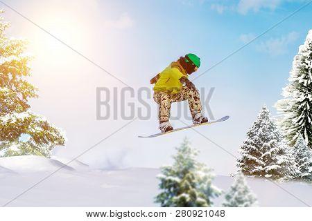 Snowboarder Jumps In Forest. Freeride Snowboarding In Ski Resort