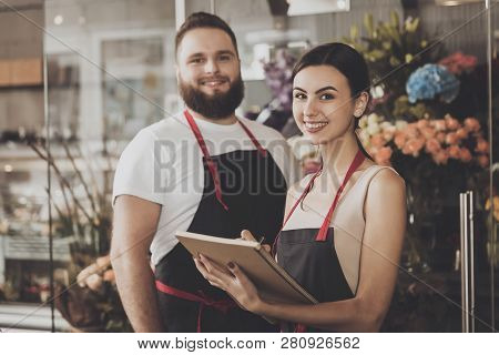 Portrait Of Smiling Florists Man And Woman. Young Bearded Man And Beautiful Girl Florists Happy With