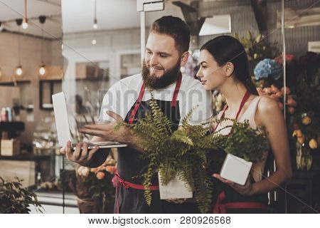 Portrait Of Smiling Florists Man And Woman. Young Bearded Man And Beautiful Smiling Girl Florists Lo