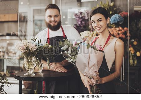 Cute Female Florist Is Standing With Bouquet Of Blue Hydrangeas And Pink Rose On Flower Market. Port