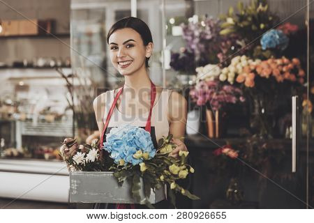 Portrait Of Beautiful Girl Florist In Flower Shop. Young Smiling Girl Florist Collects Flower Basket