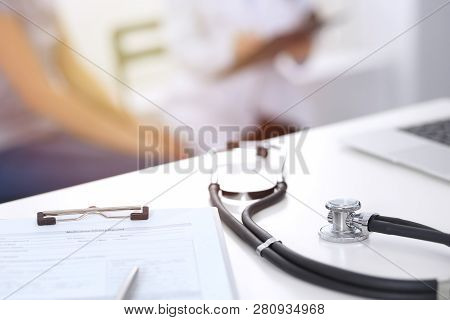 Stethoscope, Clipboard With Medical Form Lying On Hospital Reception Desk With Laptop Computer And B