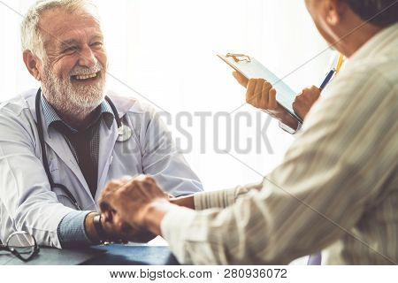 Senior Doctor Talking To Patient In The Hospital.