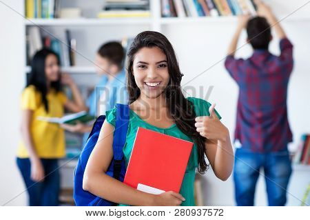Successful Latin American Female Student With Group Of Students At Library Of University