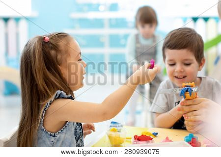 Little Kids Have A Fun Together With Colorful Modeling Clay At Daycare. Creative Kids Molding In Kin