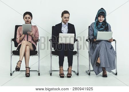 Business People Job Applicants Sitting And Waiting On Chairs In Office. Job Application And Recruitm