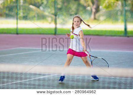 Child Playing Tennis On Indoor Court. Little Boy With Tennis Racket And Ball In Sport Club. Active E
