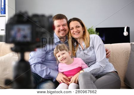 Happy Adult Millenial Family Photographed While Sitting At Home On The Couch Camera Is On A Tripod T